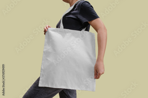 Fotomural Woman holding reusable white cotton linen eco organic fabric tote bag isolated b