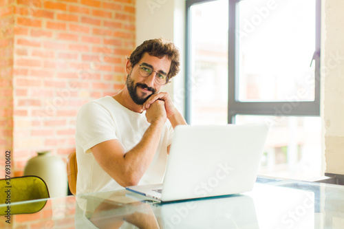 Obraz young bearded man with a laptop feeling in love and looking cute, adorable and happy, smiling romantically with hands next to face - fototapety do salonu