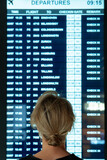Woman looking on the display with information about a flights in an airport