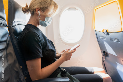 Woman wearing prevention mask during a flight inside an airplane
