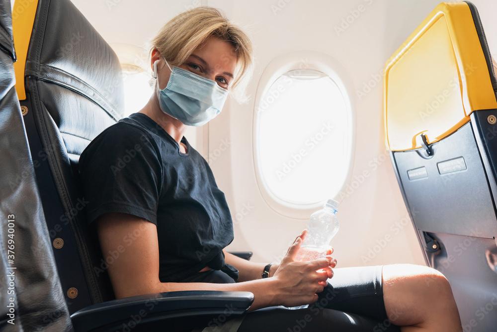 Leinwandbild Motiv - blackday : Woman wearing prevention mask during a flight inside an airplane