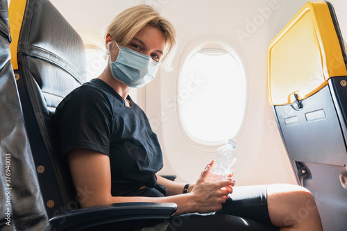 Woman wearing prevention mask during a flight inside an airplane - 376940013