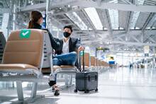 New Normal And Social Distancing Concept.Businessman And Businesswoman Wearing Face Mask Meeting During Airline Flight Status And Sitting With Distance During Coronavirus 2019 Outbreak At Airport