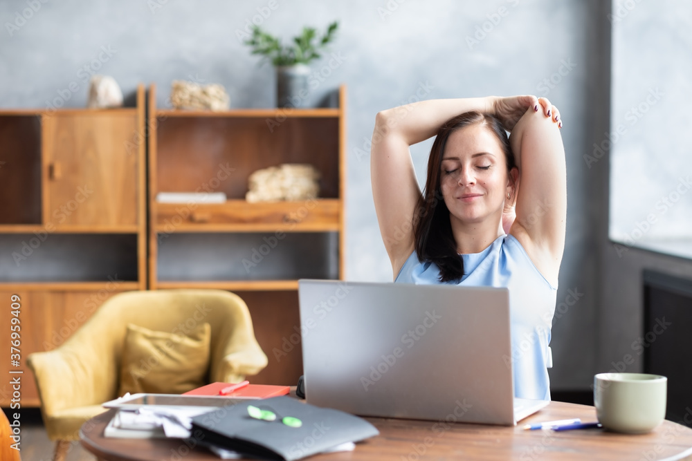 Fototapeta Caicasian young business woman stretches her body doing yoga exercise at coffee break.