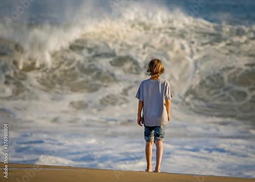 Photo Boy standing looking at high surf at Newport Beach CA