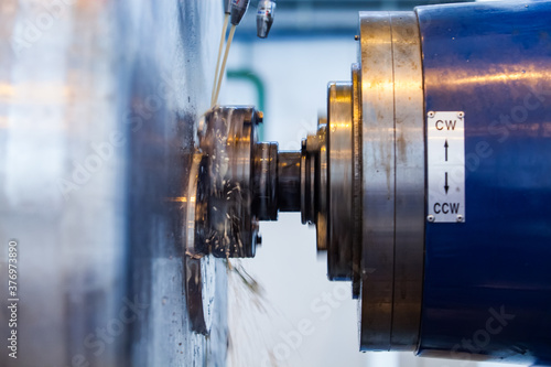 Fototapeta Cooling titanium rod with oil on metal turning lathe