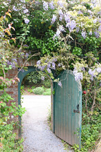 Old Gate Stands Open And Wisteria Grows Over The Brick Archway