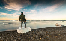 Man Standing Over A Block Of Ice