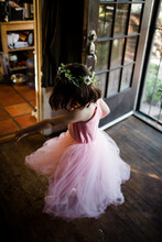 Young Girl Spinning By Front Door Wearing Tutu And Flower Crown
