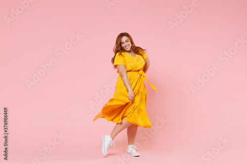 Fotografia Full length portrait of smiling beautiful charming young redhead plus size body positive female woman girl 20s in yellow dress posing looking camera isolated on pastel pink color background studio
