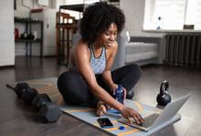 Black Sportswoman Using Laptop...