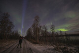 young man lighting northern lights with his flashlight