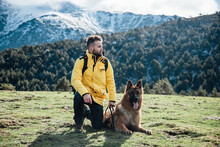 Young Man With Yellow Jacket And Backpack Plays With German Shepherd Dog In The Mountains.