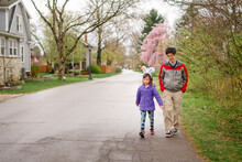 A Child Wearing Bunny Ears Walks With Her Father On Street In Spring