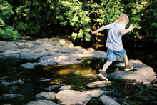 A Brave 5 Year Old Jumping Over Rocks In A River