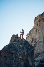 Male Climber Reading A Guide Book On The Top Of The Boulder In Oregon