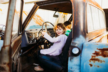 Young Brother And Sister Sitting In Vintage Truck At Sunset