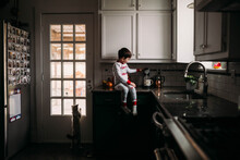Young Boy Sitting On Counter Making Coffee With Cat Looking Out Window