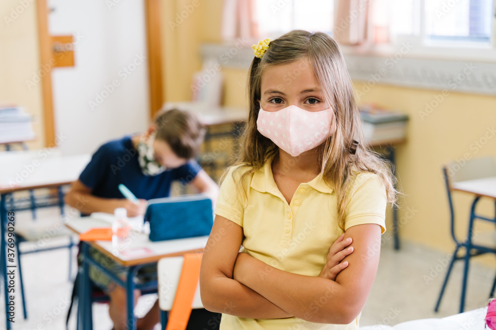 Fototapeta Children in their school classroom wearing masks during the covid pandemic