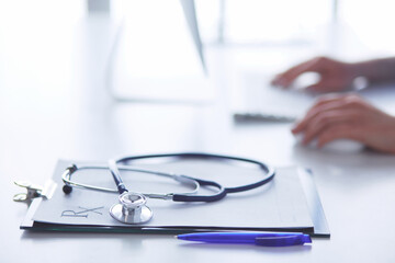 Close-up of stethoscope is lying on the table near female doctor typing on laptop computer