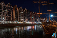 Gdansk, North Poland - August 13, 2020: Night Photograph Of Medieval Style Polish Architecture And A Pirate Ship Over Motlawa River Located In The Old Town Near Baltic Sea