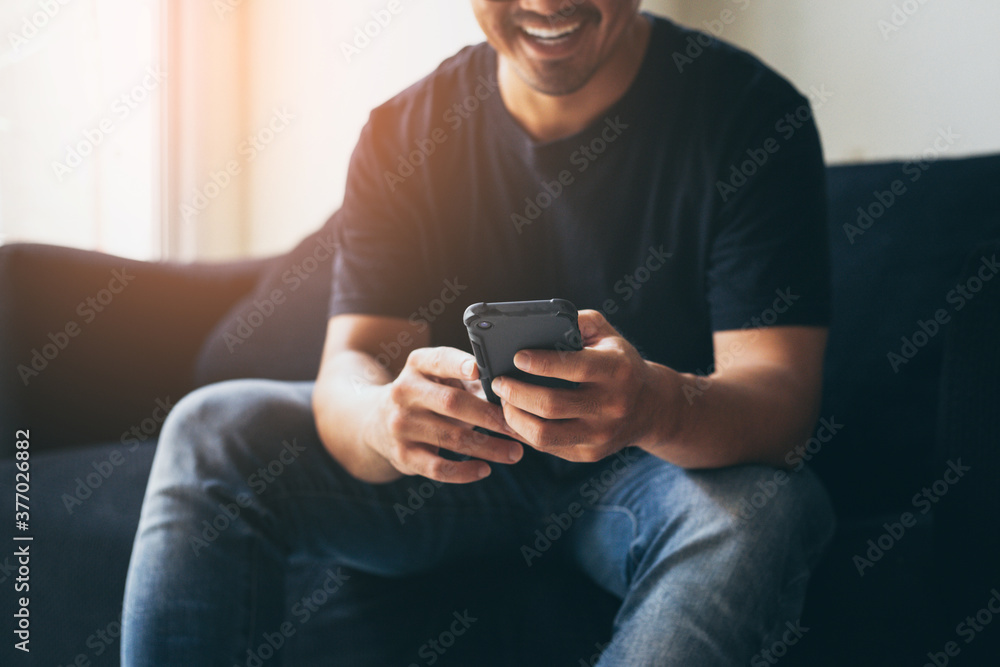 Fototapeta using cell phone.hand holding texting message on screen mobile chatting,search internet information sitting on sofa.technology device contact communication connecting people concept