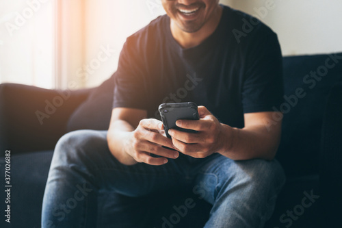 Obraz using cell phone.hand holding texting message on screen mobile chatting,search internet information sitting on sofa.technology device contact communication connecting people concept - fototapety do salonu