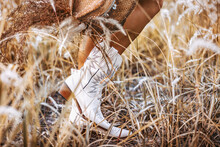 Close Up Of Young Woman Legs Wearing Cowgirl Boots On The Field