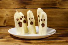 Homemade Halloween Scary Banana Ghosts Monsters With Chocolate Faces. Funny Dessert For Halloween Party On Wooden Table