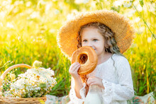 Beautiful Little Girl Sitting In A Straw Hat In A Yellow Field With Wild Flowers With A Bottle Of Milk And A Bagel, Picnic In The Field