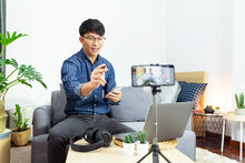 Social Media Influencer Or Blogger Present And Review Recording Or Streaming Vlog About Product Using Smartphone On Tripod For Social Media Channel Making Live Stream Concept.