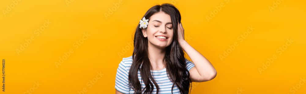 Fototapeta brunette young woman with flowers in hair and closed eyes smiling isolated on yellow, panoramic shot