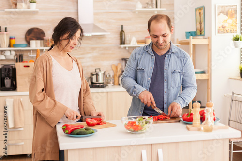 Photo Young couple cutting tomatoes for salad in kitchen using cutting board