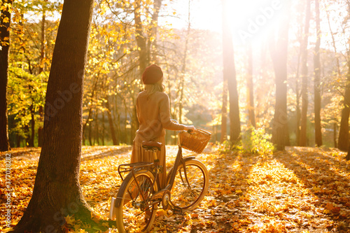 Fototapeta Autumn woman in autumn park. Happy young woman posing with bike in autumn forest. obraz na płótnie