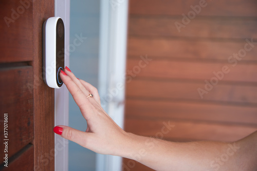 Obraz na plátne Close Up Of Woman Ringing Front Doorbell Equipped With Security Video Camera