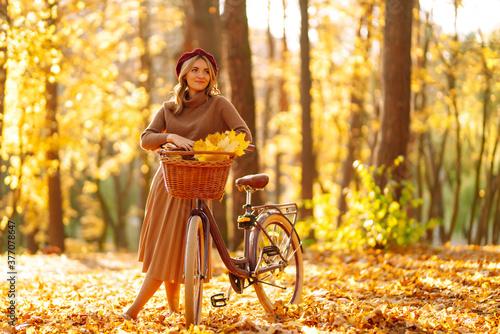 Fototapeta Autumn woman in autumn park. Happy young woman posing with bike in autumn forest. obraz na płótnie