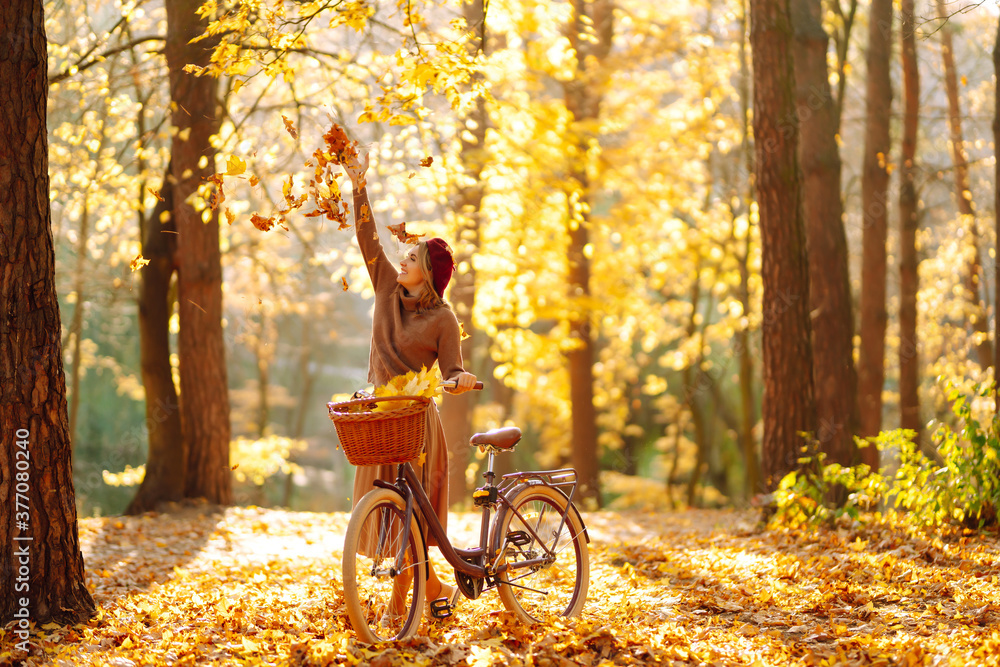 Fototapeta Happy young woman having fun and playing with autumn yellow leaves in autumn park.  Relaxation, enjoying, solitude with nature. - obraz na płótnie