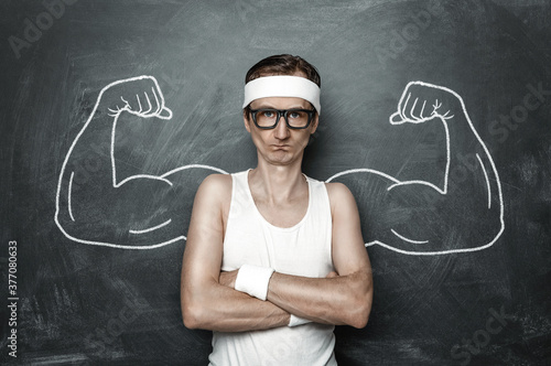 Funny sport nerd with fake muscle drawn on the chalkboard Fototapeta