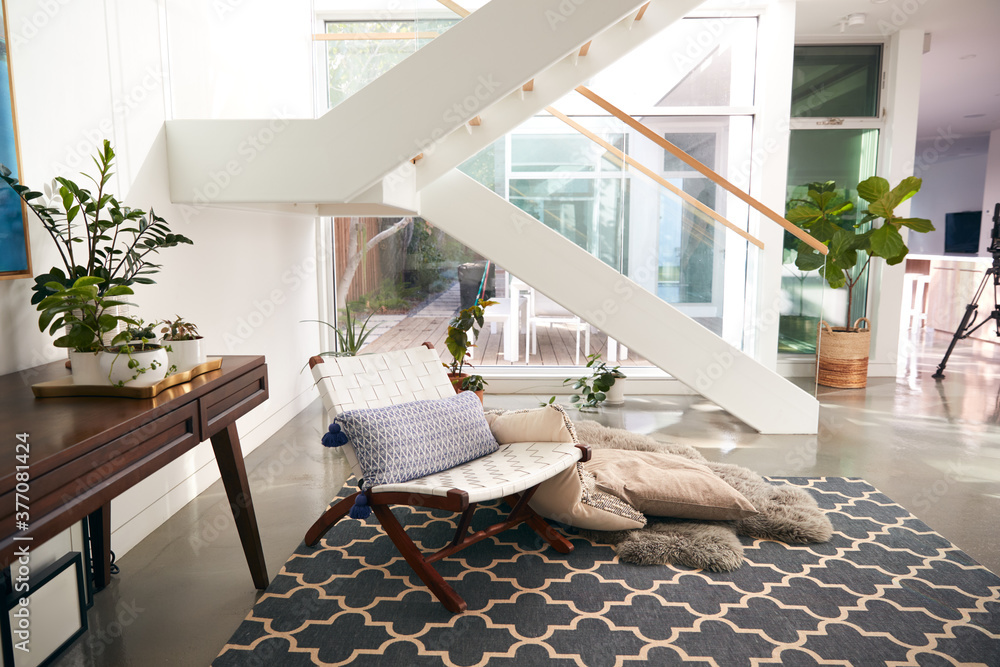 Fototapeta Interior View Of Beautiful Living Area With Glass Staircase And Soft Furnishings In New Family Home
