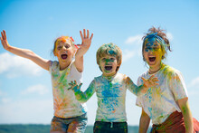 Funny Kids Face In Color Splash, Coloured Powder On Children Body. Cheerful Friends Showing Hands Painted In Bright Colors. Colorful Dirty People.