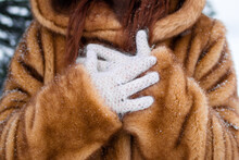 Woman's Hands In White Knitted Gloves Close Up. Woman In Faux Fur Coat With Snowflakes.