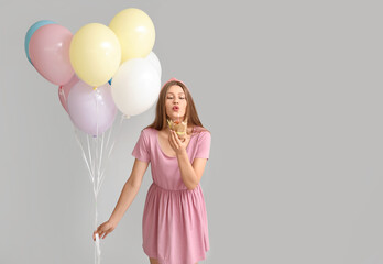 Fototapeta Boks Young woman with balloons and birthday cake on grey background