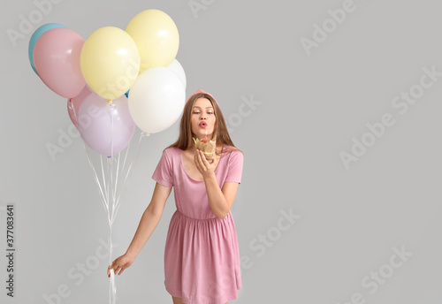 Young woman with balloons and birthday cake on grey background - 377083641