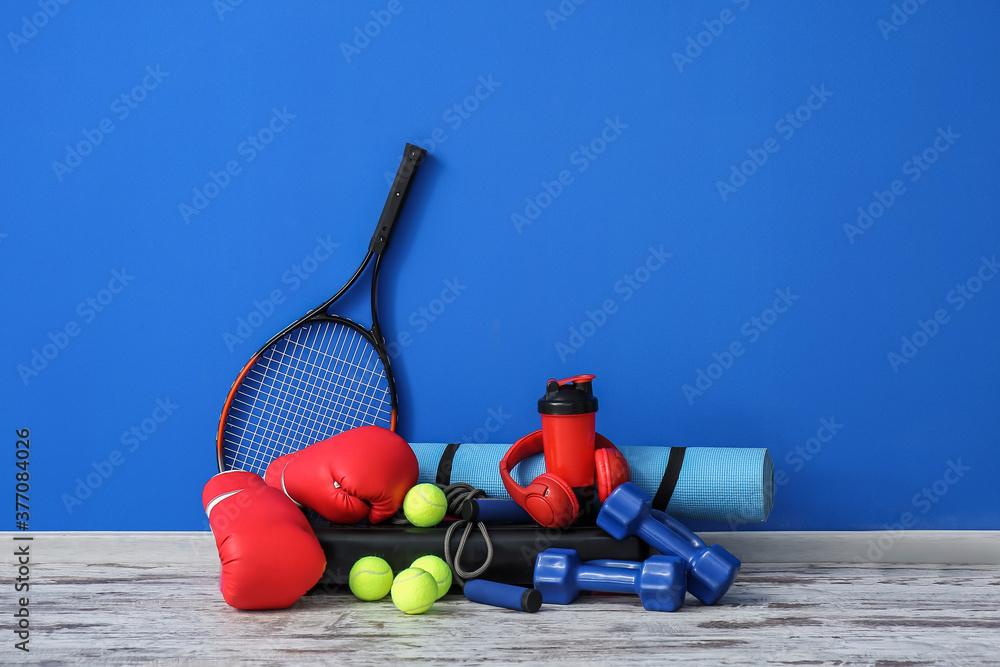 Fototapeta Set of sport equipment on floor near color wall