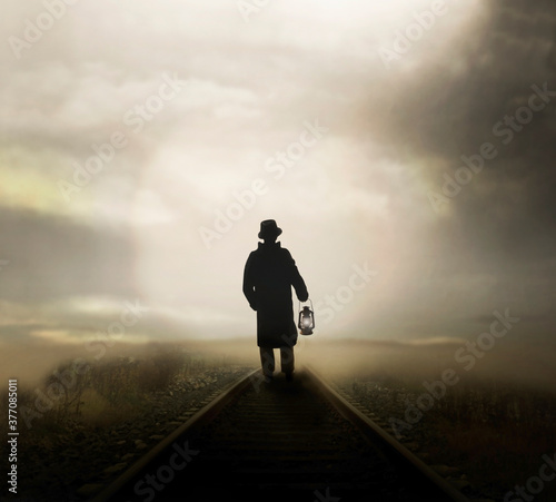Stampa su Tela man walks on the rail road with a lantern following the light that comes from af