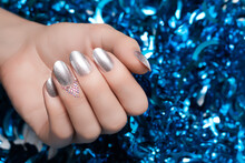 Female Hand With Christmas Nail Design. Silver Nail Polish Manicure. Female Hand On Blue New Year Tinsel Background.
