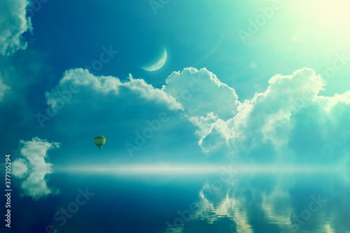 Photo Amazing heavenly image - crescent and hot air balloon rising above serene sea, light from heaven