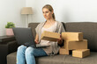 Leinwandbild Motiv young woman small online business owner sitting on couch and preparing package for shipping on laptop at home. sme entrepreneur