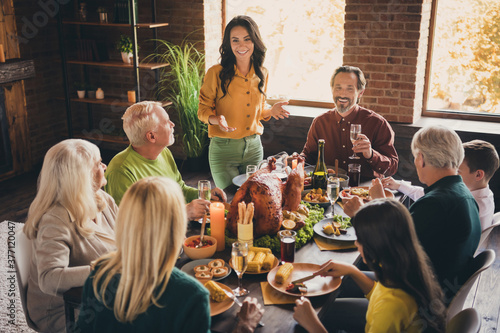 Obraz Portrait of nice attractive cheerful family friends friendship parents meeting eating festal luncheon turkey drinking champagne mom saying toast at modern loft brick industrial interior - fototapety do salonu