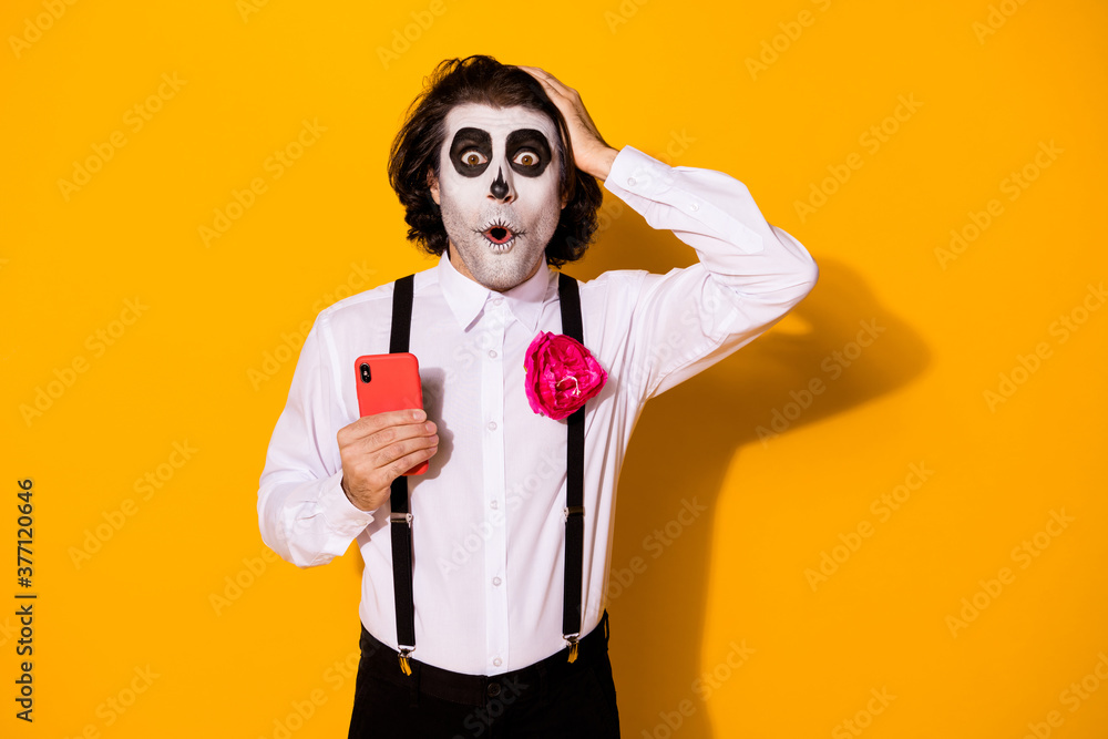 Fototapeta Portrait of his he nice handsome spooky wondered stunned astonished amazed guy using device fake news calavera blog post comment reaction isolated bright vivid shine vibrant yellow color background